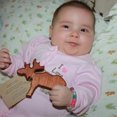 baby holding rustic wood toy