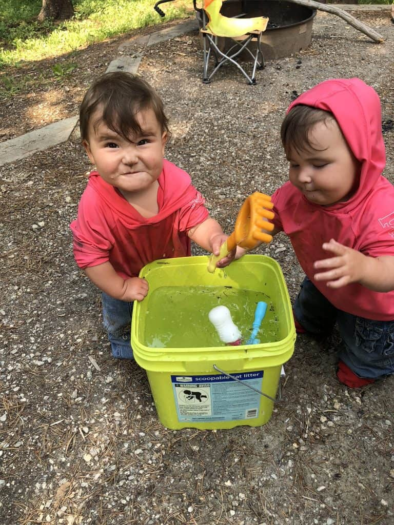use a bucket of water to keep babies busy around camp!