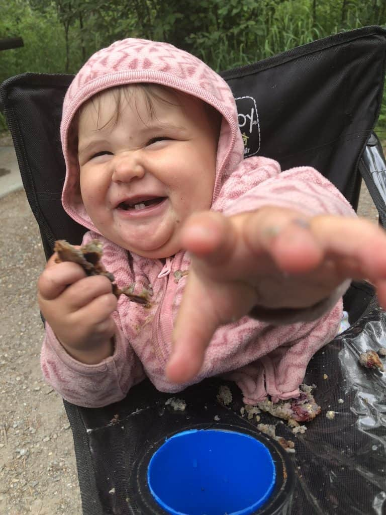 keeping babies busy around camp with food in a camping highchair