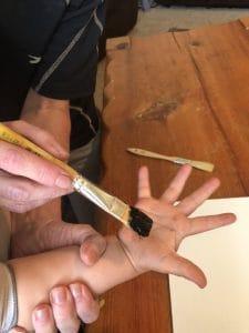 making handprint flower art with toddler