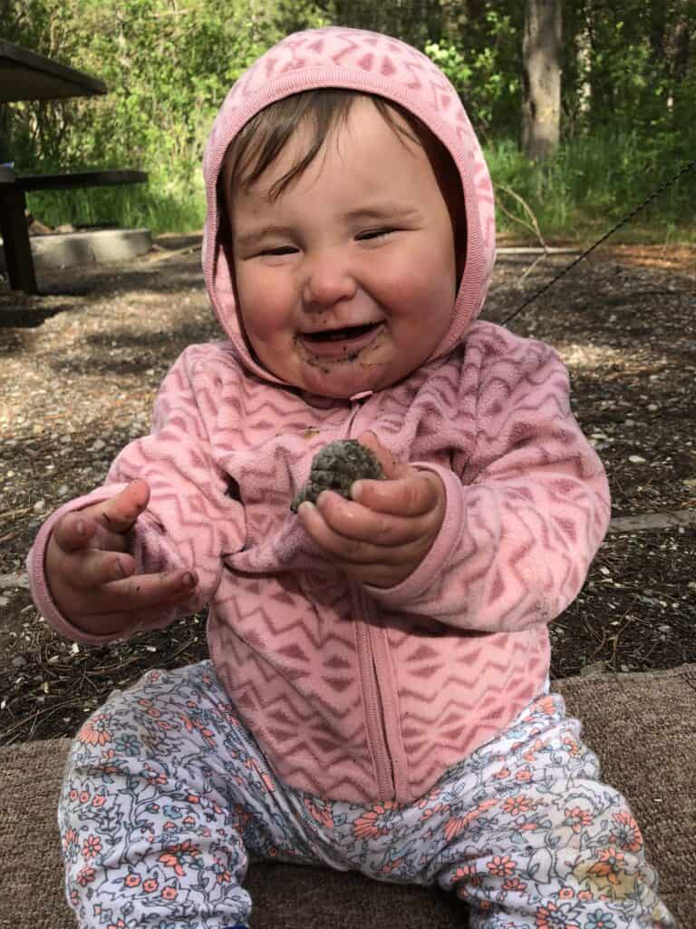 baby play with pinecone in nature
