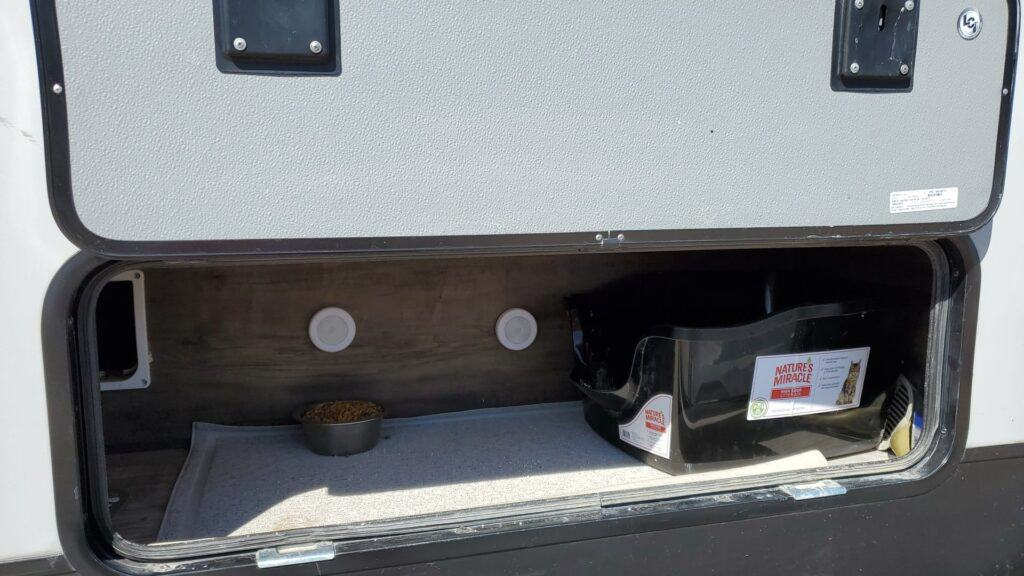 litter box set up in storage compartment of camper
