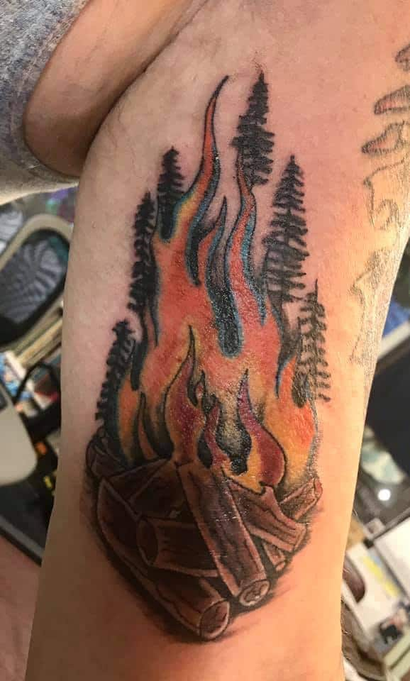 campfire and pines tattoo arm