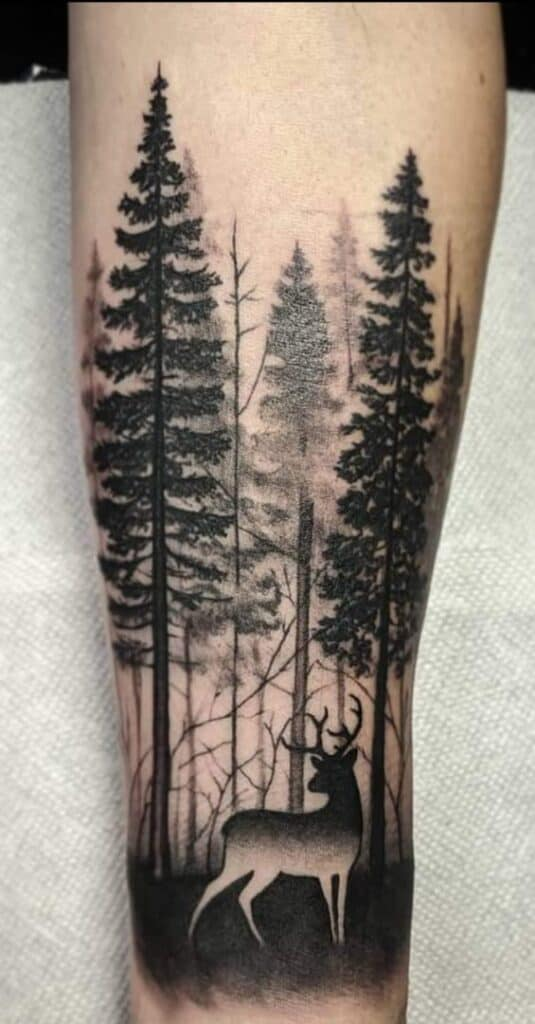 black and white deer in pine forest on forearm tattoo