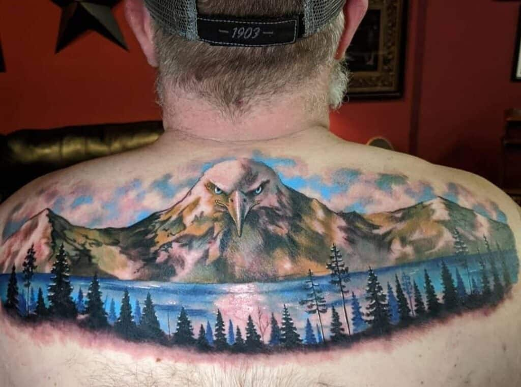 full color mountain and lake scene with eagle in mountains back shoulders tattoo men